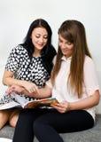 Dos muchachas bonitas que leen el compartimiento Fotos de archivo libres de regalías