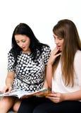 Dos muchachas bonitas que leen el compartimiento Imágenes de archivo libres de regalías
