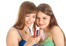 Dos muchachas bonitas que leen SMS en el teléfono móvil Imagenes de archivo