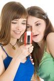 Dos muchachas bonitas que leen SMS en el teléfono móvil Fotos de archivo