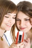 Dos muchachas bonitas que leen SMS en el teléfono móvil Imagen de archivo libre de regalías