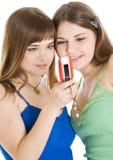 Dos muchachas bonitas que leen SMS en el teléfono móvil Foto de archivo libre de regalías