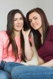 Dos muchachas bonitas que llaman alguien con un teléfono móvil Imagen de archivo libre de regalías