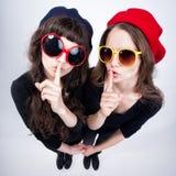 Dos muchachas bonitas que muestran silenciosamente con sus fingeres cruzan sus labios Fotos de archivo