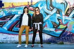 Dos muchachas bonitas que presentan en un día de primavera delante de la pintada en la pared en fondo Imágenes de archivo libres de regalías