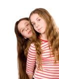 Dos muchachas bonitas que se colocan aisladas en blanco Fotos de archivo libres de regalías