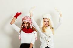 Dos muchachas calientan la ropa del invierno que se divierte Imagenes de archivo
