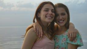 Dos muchachas caucásicas jovenes en los vestidos que abrazan en el lago, riendo, sonriendo, naturaleza en el fondo, mirando la cá metrajes