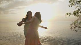 Dos muchachas caucásicas jovenes en los vestidos que corren a través de la arena en el mar, risa, abrazando, luz del sol, puesta  almacen de metraje de vídeo