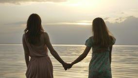 Dos muchachas caucásicas jovenes en vestidos que caminan en agua poco profunda en la puesta del sol almacen de metraje de vídeo