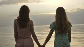 Dos muchachas caucásicas jovenes en vestidos que caminan a lo largo del agua poco profunda en la puesta del sol, vuelven y miran  metrajes