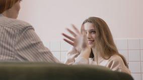Dos muchachas caucásicas jovenes que se sientan en un café y que sonríen, hablando, diálogo, fps del concepto 60 del chisme metrajes