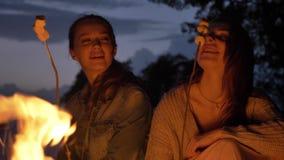 Dos muchachas caucásicas jovenes se sientan por la tarde por el fuego en naturaleza, cocinando el marshmelow, sonriendo, comiendo metrajes