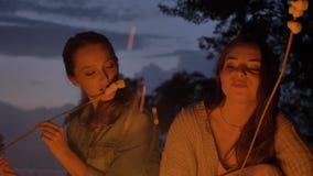 Dos muchachas caucásicas jovenes se sientan por la tarde por el fuego en naturaleza, comiendo el marshmelow, mirando un fuego abi almacen de metraje de vídeo