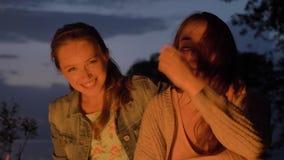 Dos muchachas caucásicas jovenes se sientan por la tarde por el fuego en la naturaleza, riendo, sonriendo almacen de video