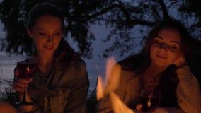 Dos muchachas caucásicas jovenes se sientan por la tarde por el fuego en la naturaleza, vino de la bebida, sonriendo metrajes