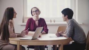 Dos muchachas caucásicas positivas hermosas hablan con el hombre japonés en una entrevista de trabajo por la tabla en oficina san
