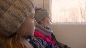 Dos muchachas caucásicas que miran a través de ventana Las chicas jóvenes viajan en un tren almacen de video