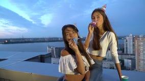 Dos muchachas celebran un cumpleaños en el tejado del edificio con los casquillos y los silbidos tarde en la noche en tiempo vent almacen de metraje de vídeo