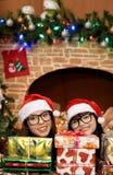 Dos muchachas cerca de la chimenea y del árbol de navidad Foto de archivo libre de regalías