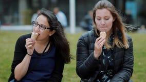 Dos muchachas comen el helado en un día soleado - cámara lenta almacen de metraje de vídeo