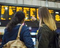Dos muchachas comprueban la tabla de la salida en una estación de tren Fotografía de archivo libre de regalías