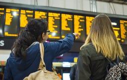 Dos muchachas comprueban la tabla de la salida en una estación de tren Fotos de archivo