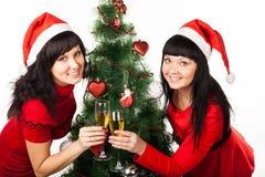 Dos muchachas con champán cerca del árbol de navidad Fotos de archivo