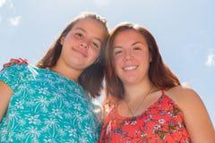 Dos muchachas con el cielo azul y la luz del sol en el fondo Imagen de archivo
