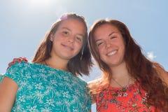 Dos muchachas con el cielo azul y la luz del sol en el fondo Foto de archivo libre de regalías