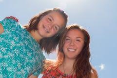Dos muchachas con el cielo azul y la luz del sol en el fondo Fotos de archivo libres de regalías