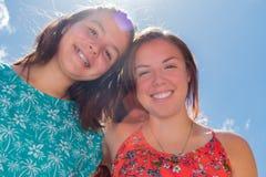 Dos muchachas con el cielo azul y la luz del sol en el fondo Imagen de archivo libre de regalías