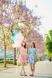 Dos muchachas con el manojo de globos delante de la torre Eiffel fotos de archivo libres de regalías