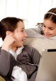Dos muchachas con el ordenador de la tablilla de tacto Imágenes de archivo libres de regalías