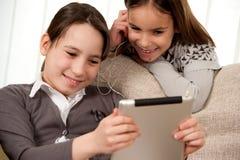 Dos muchachas con el ordenador de la tablilla de tacto Fotos de archivo
