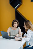 Dos muchachas con el ordenador portátil en la tabla Foto de archivo libre de regalías
