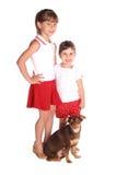 Dos muchachas con el perro aislado en blanco Foto de archivo