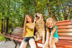 Dos muchachas con el perro feliz Imagenes de archivo