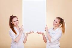 Dos muchachas con el tablero de la presentación en blanco Imagen de archivo