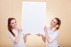 Dos muchachas con el tablero de la presentación en blanco Foto de archivo libre de regalías
