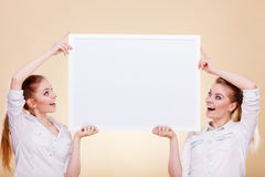Dos muchachas con el tablero de la presentación en blanco Imágenes de archivo libres de regalías