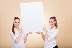 Dos muchachas con el tablero de la presentación en blanco Fotografía de archivo libre de regalías