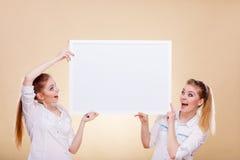 Dos muchachas con el tablero de la presentación en blanco Fotos de archivo