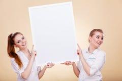 Dos muchachas con el tablero de la presentación en blanco Fotografía de archivo