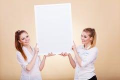 Dos muchachas con el tablero de la presentación en blanco Imagenes de archivo