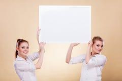Dos muchachas con el tablero de la presentación en blanco Fotos de archivo libres de regalías