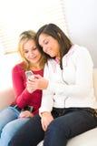Dos muchachas con el teléfono celular Foto de archivo