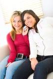 Dos muchachas con el teléfono celular Imagenes de archivo