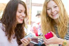 Dos muchachas con el teléfono elegante Imagen de archivo