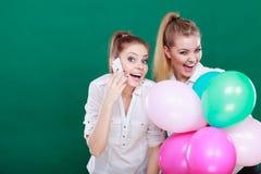 Dos muchachas con el teléfono móvil y los globos Fotos de archivo